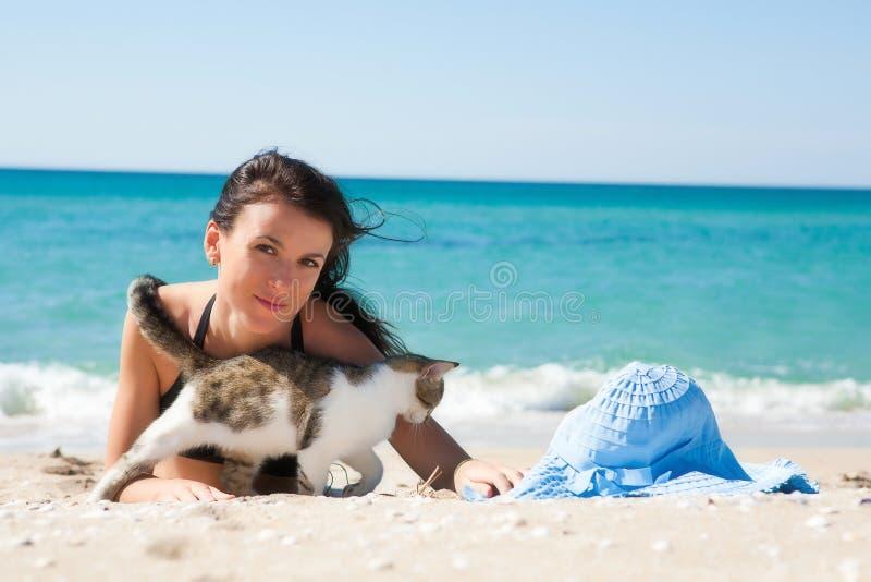 Ragazza sulla spiaggia con un gattino immagine stock