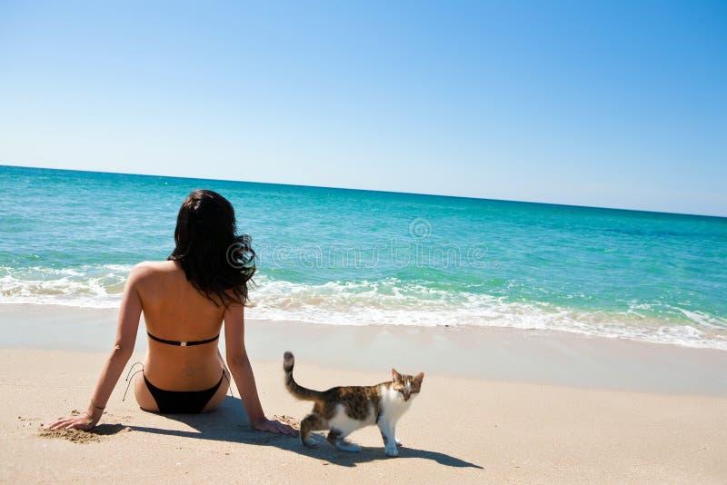 Ragazza sulla spiaggia con un gattino fotografie stock