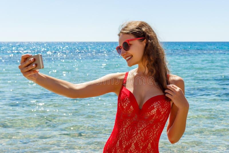 Ragazza sulla spiaggia con un telefono cellulare che fa selfie il giorno soleggiato fotografie stock