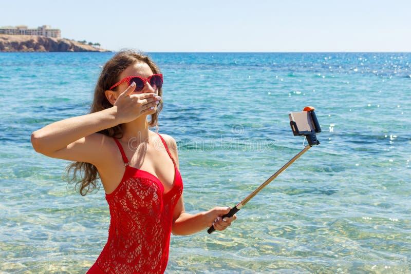 Ragazza sulla spiaggia con un telefono cellulare che fa selfie il giorno soleggiato immagine stock