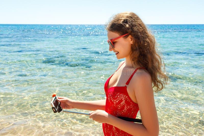 Ragazza sulla spiaggia con un telefono cellulare che fa selfie il giorno soleggiato immagine stock libera da diritti