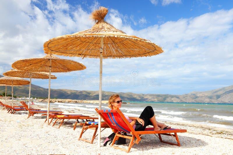 Ragazza sulla spiaggia sotto paglia immagini stock libere da diritti