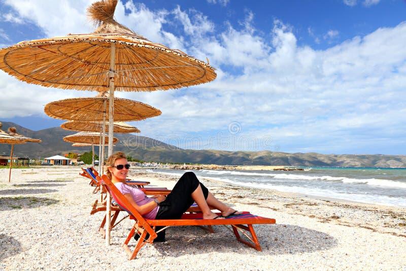 Ragazza sulla spiaggia sotto un parasole fotografia stock
