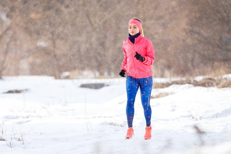 Ragazza sulla traccia che esegue addestramento nell'inverno fotografia stock libera da diritti