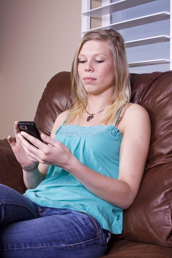 Ragazza sullo strato con il suo telefono delle cellule immagine stock