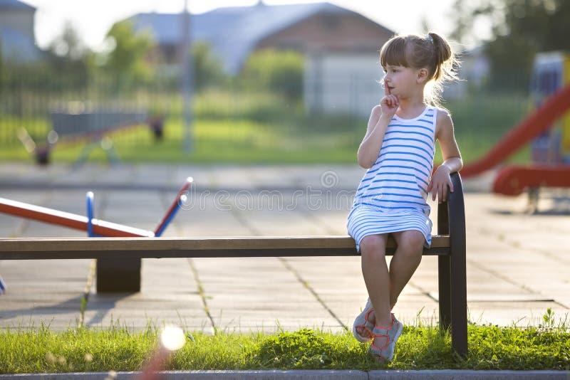 Ragazza sveglia in breve vestito che si siede da solo all'aperto sul banco del campo da giuoco il giorno di estate soleggiato immagini stock