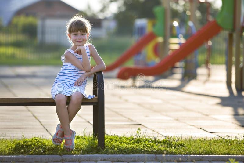 Ragazza sveglia in breve vestito che si siede da solo all'aperto sul banco del campo da giuoco il giorno di estate soleggiato immagine stock libera da diritti