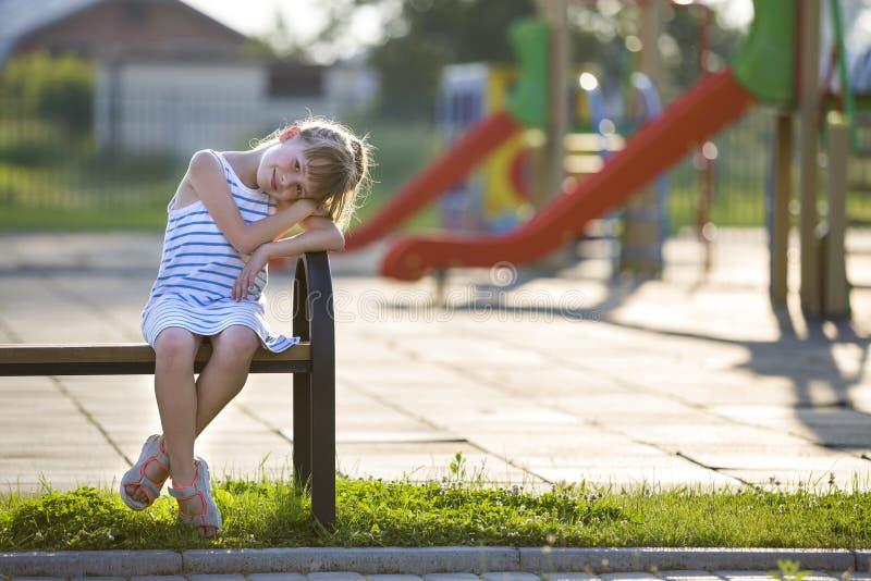 Ragazza sveglia in breve vestito che si siede da solo all'aperto sul banco del campo da giuoco il giorno di estate soleggiato fotografie stock