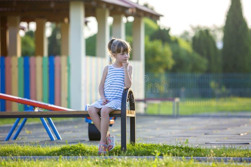 Ragazza sveglia in breve vestito che si siede da solo all'aperto sul banco del campo da giuoco il giorno di estate soleggiato fotografia stock