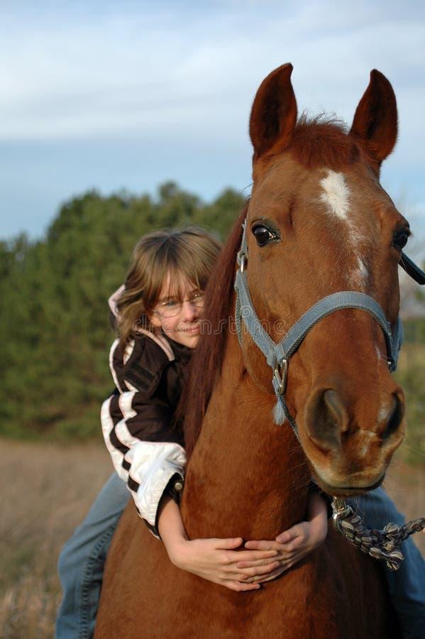 Ragazza sveglia che abbraccia cavallo immagine stock