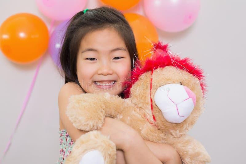 Ragazza sveglia che abbraccia giocattolo molle ad una festa di compleanno immagine stock libera da diritti