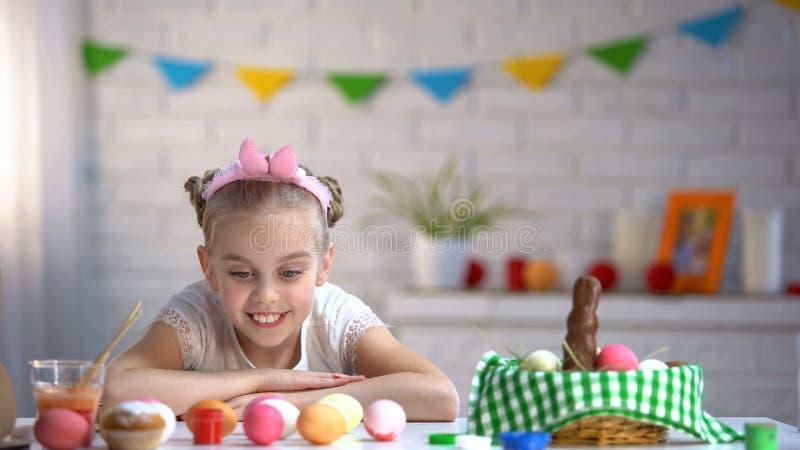 Ragazza sveglia che ammira le uova variopinte, preparanti per pasqua domenica, infanzia felice fotografie stock
