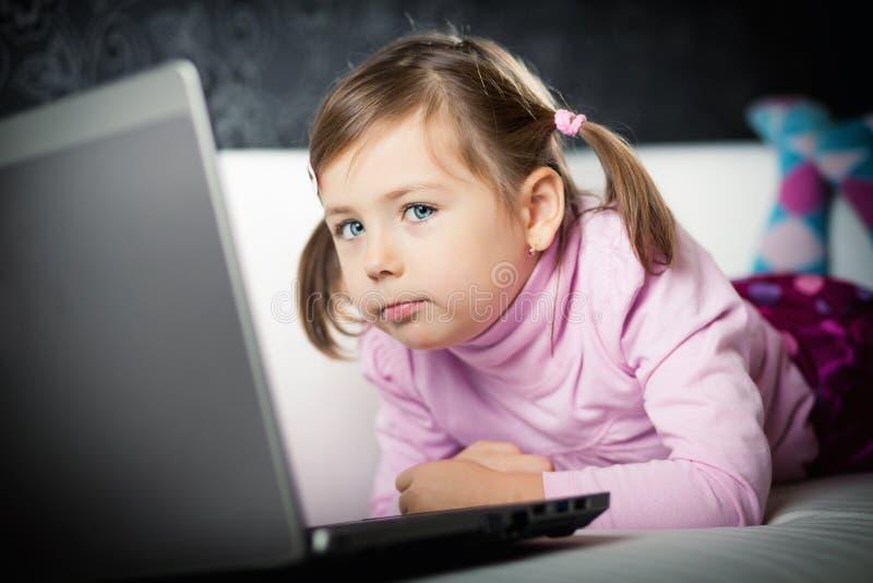 Ragazza sveglia che esamina computer portatile immagine stock