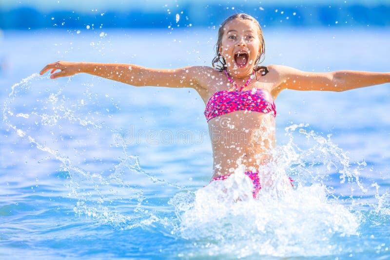 Ragazza sveglia che gioca nel mare La ragazza pre-teenager felice gode dell'acqua e delle feste dell'estate nelle destinazioni di immagine stock libera da diritti