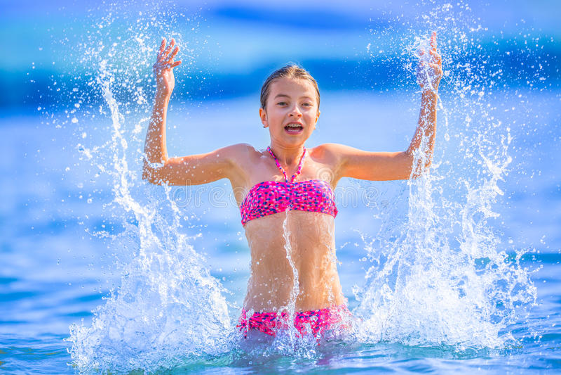 Ragazza sveglia che gioca nel mare La ragazza pre-teenager felice gode dell'acqua e delle feste dell'estate nelle destinazioni di fotografia stock