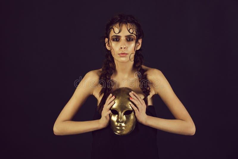 Ragazza sveglia che giudica dorata, carnevale, maschera di protezione immagine stock