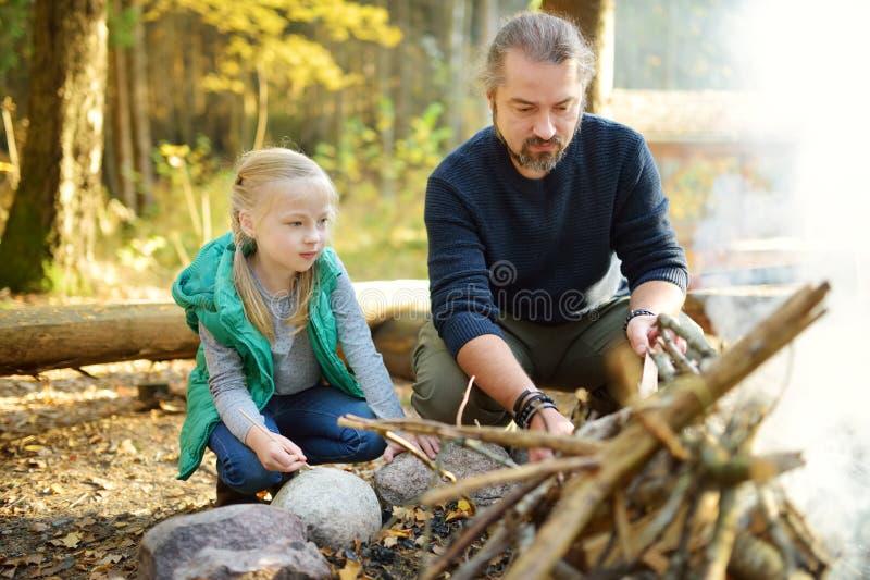 Ragazza sveglia che impara iniziare un falò Padre che insegna a sua figlia a fare un fuoco Bambino divertendosi al fuoco del camp fotografia stock