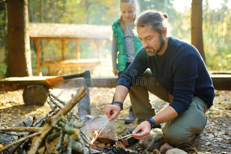 Ragazza sveglia che impara iniziare un falò Padre che insegna a sua figlia a fare un fuoco Bambino divertendosi al fuoco del camp immagini stock libere da diritti