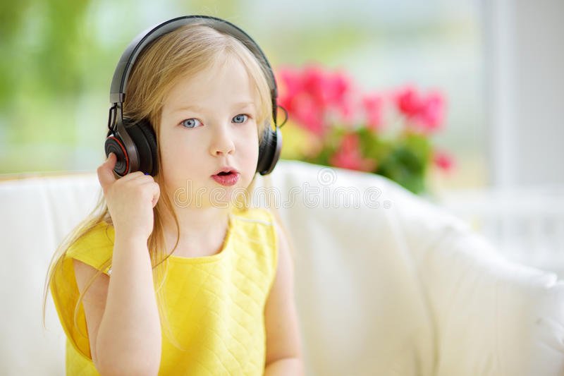 Ragazza sveglia che indossa le cuffie senza fili enormi Bambino grazioso che ascolta la musica Scolara divertendosi ascoltare le  immagini stock
