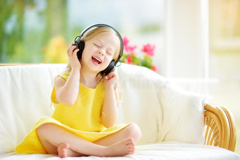 Ragazza sveglia che indossa le cuffie senza fili enormi Bambino grazioso che ascolta la musica Scolara divertendosi ascoltare le  immagine stock