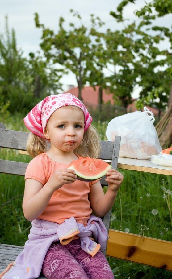 Ragazza sveglia che mangia anguria fotografia stock libera da diritti