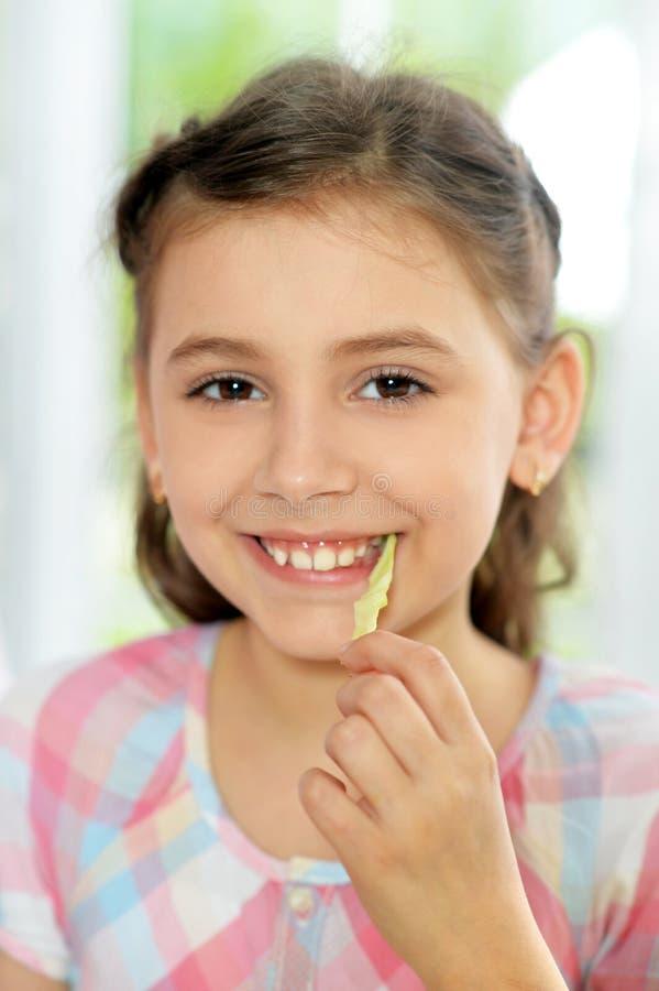 Ragazza sveglia che mangia insalata fresca deliziosa in cucina fotografie stock libere da diritti