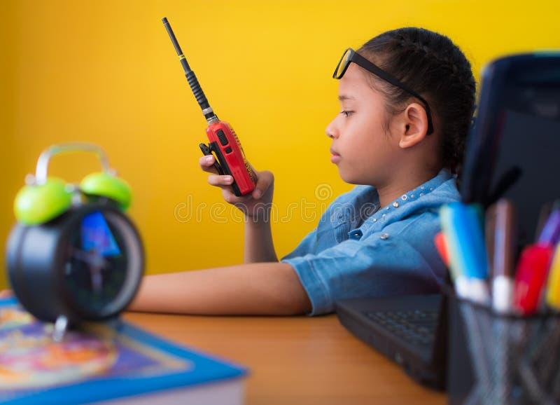 Ragazza sveglia che per mezzo del walkie-talkie allo scrittorio funzionante con il fondo giallo del computer portatile fotografia stock