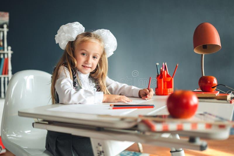 Ragazza sveglia che si siede alla tavola ed al disegno Ritratto di bella ragazza nell'aula Scolara con gli archi bianchi che si s immagine stock libera da diritti