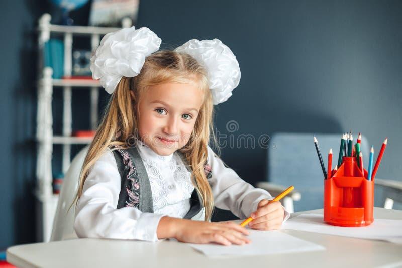 Ragazza sveglia che si siede alla tavola ed al disegno Ritratto di bella ragazza nell'aula Scolara con gli archi bianchi che si s fotografia stock