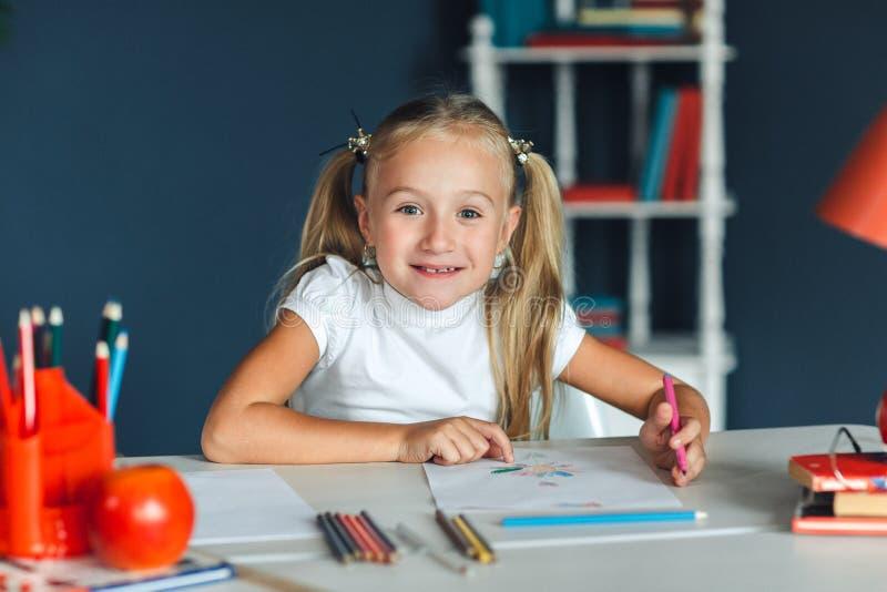 Ragazza sveglia che si siede alla tavola ed al disegno Ritratto di bella ragazza nell'aula Scolara che si siede alla tavola che e fotografia stock