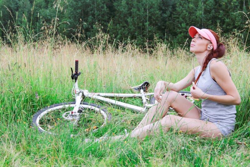 Ragazza sveglia che si siede sull'erba che ascolta la musica da parte a parte immagine stock