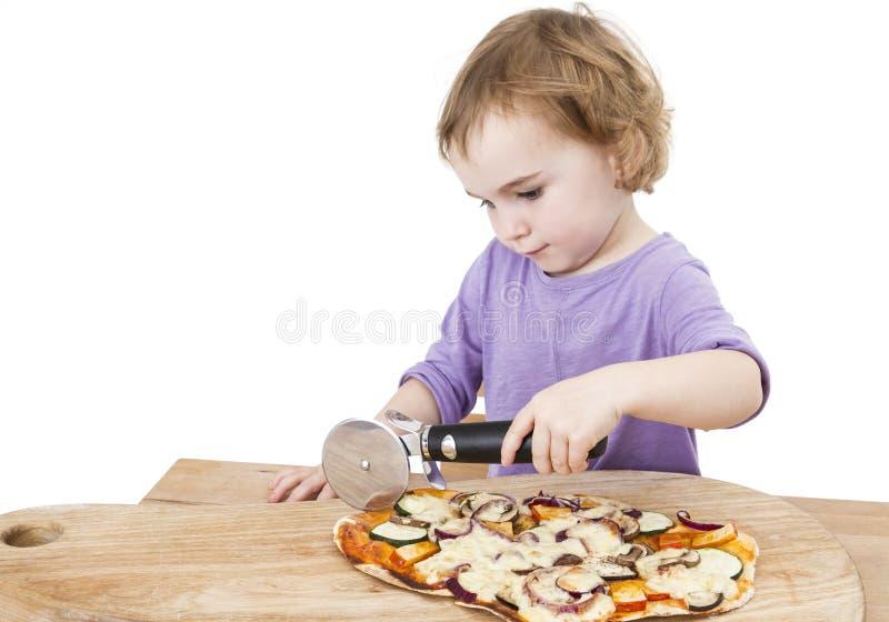 Ragazza sveglia che taglia pizza casalinga fresca immagine stock libera da diritti