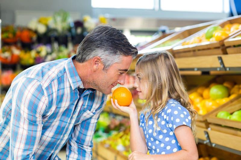 Ragazza sveglia che tiene un'arancia a suo padre immagini stock