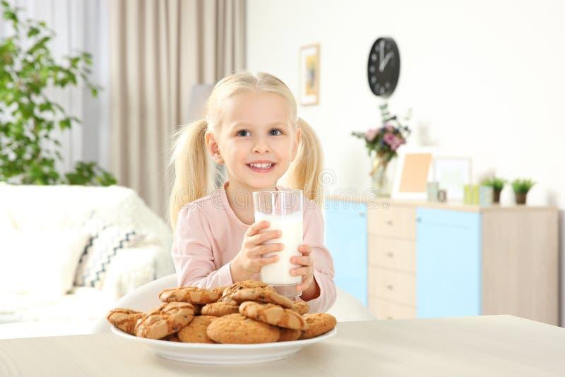 Ragazza sveglia con bicchiere di latte ed i biscotti fotografia stock libera da diritti