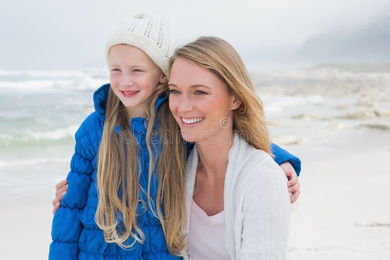 Ragazza sveglia con la madre sorridente alla spiaggia immagini stock libere da diritti