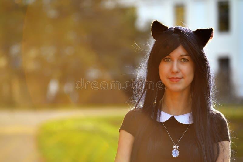Ragazza sveglia con le orecchie di gatto del giocattolo sulla testa alla luce del raggio di sole immagine stock libera da diritti
