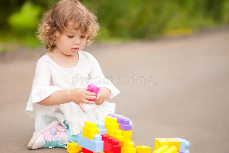 Ragazza sveglia del bambino che gioca con i blocchetti del costruttore fotografia stock