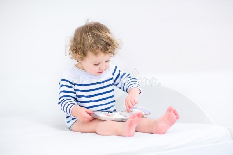 Ragazza sveglia del bambino che legge un libro in camera da letto bianca immagini stock libere da diritti