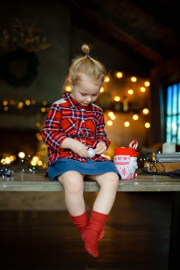 Ragazza sveglia del bambino che mangia l'uovo di cioccolato che si siede in una casa cercante decorata per il Natale Il concetto  immagini stock libere da diritti