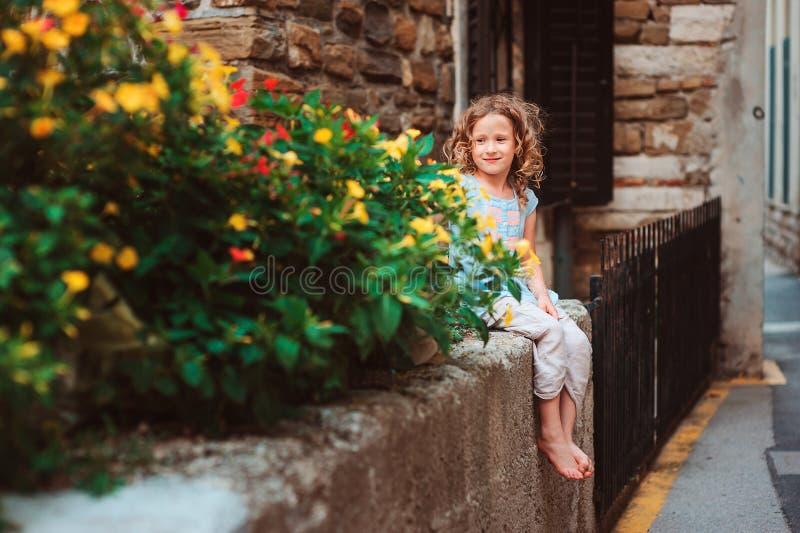 Ragazza sveglia del bambino che si siede sui fiori degli odori e della parete di pietra fotografia stock