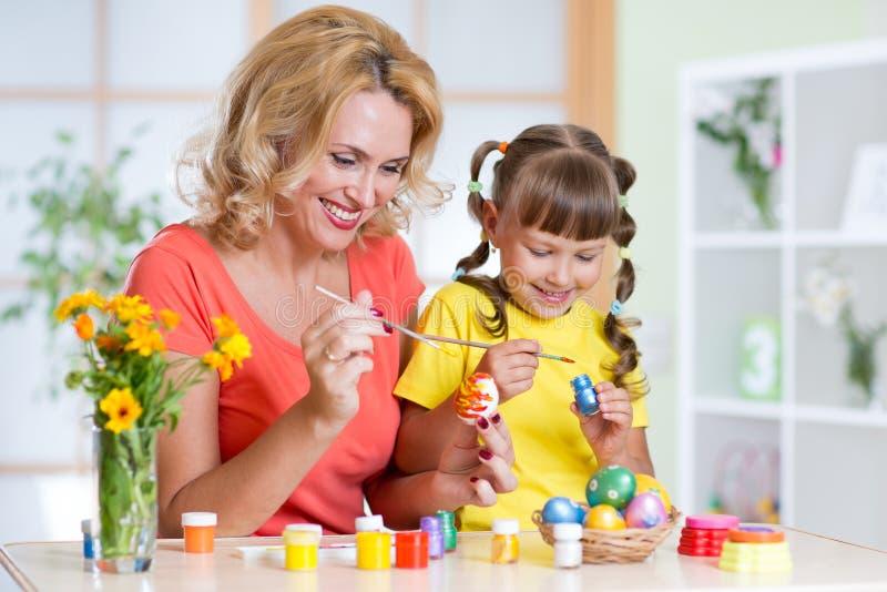 Ragazza sveglia del bambino e della donna che decora le uova di Pasqua a casa immagini stock libere da diritti
