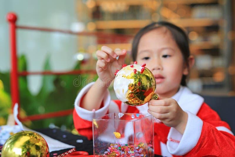 Ragazza sveglia del piccolo bambino che fa l'ornamento della decorazione della palla di Natale Decorazioni fatte a mano del nuovo immagini stock libere da diritti