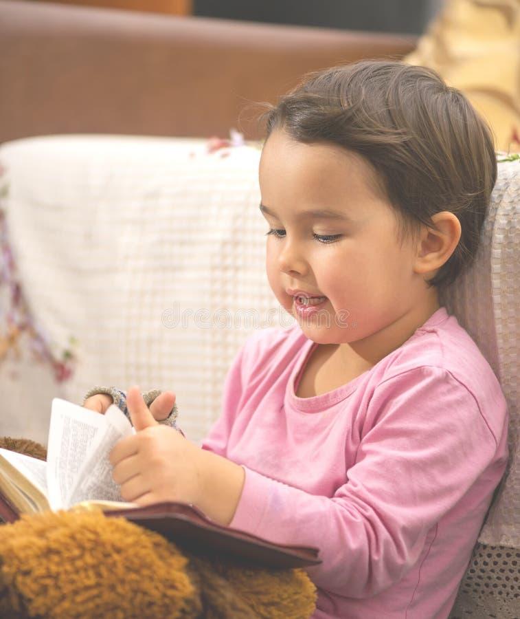 Ragazza sveglia del piccolo bambino che legge la bibbia fotografia stock libera da diritti