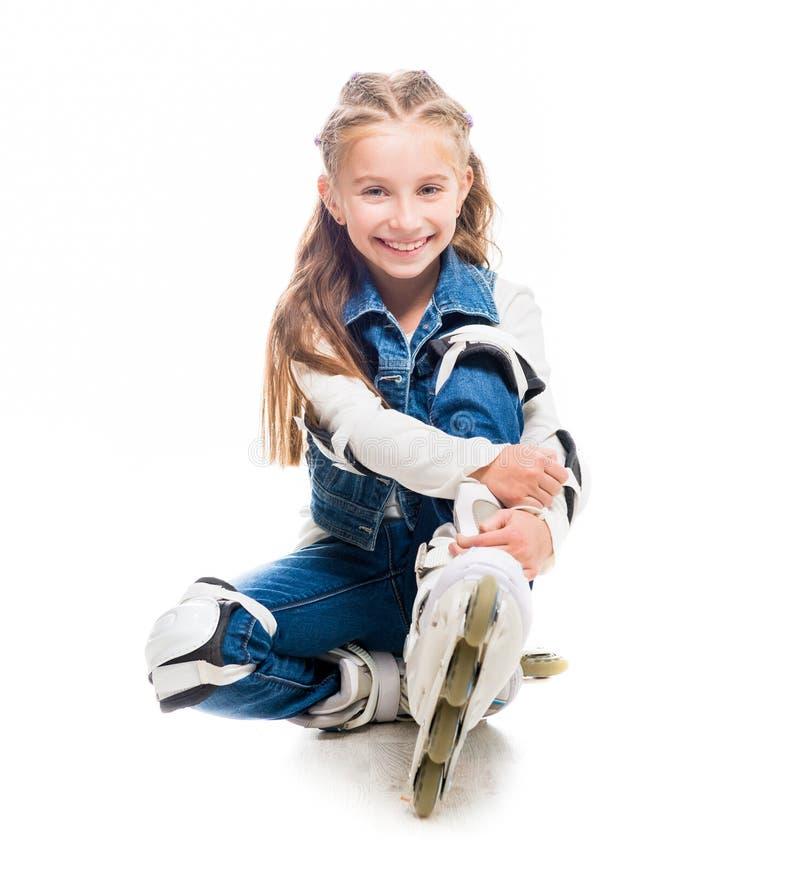Ragazza sveglia dell'adolescente sulla seduta dei rollerskates fotografie stock libere da diritti