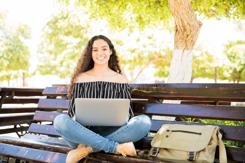 Ragazza sveglia della High School con il computer portatile sul banco di parco fotografia stock libera da diritti