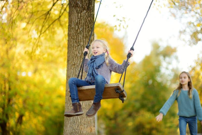 Ragazza sveglia divertendosi su un'oscillazione nel parco soleggiato di autunno Fine settimana della famiglia in una città immagini stock