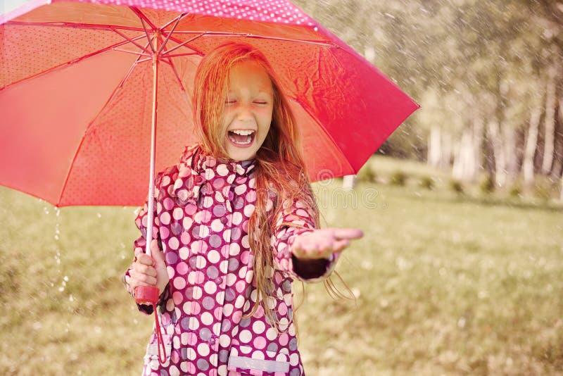 Ragazza sveglia durante la pioggia fotografie stock libere da diritti