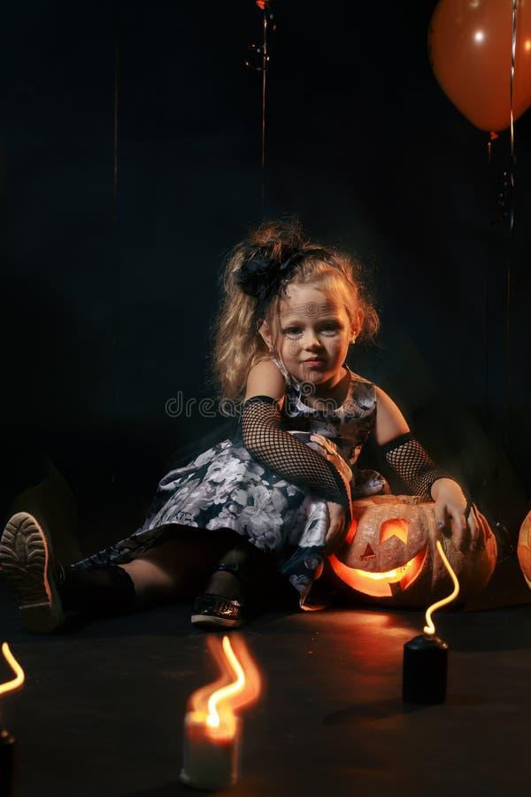 Ragazza sveglia e graziosa con i riccioli lunghi che posano per Halloween che porta un cappello nero ed arancio enorme immagini stock libere da diritti