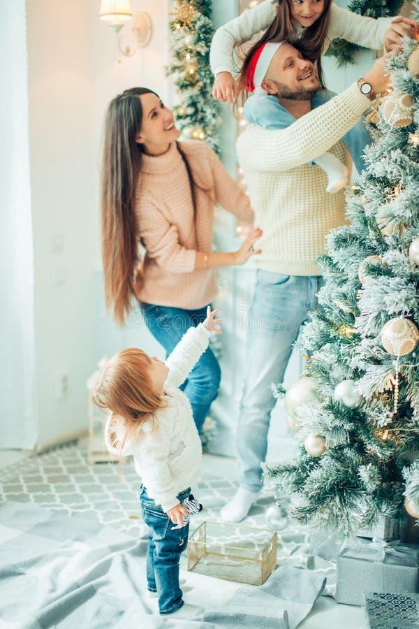 Ragazza sveglia e sua la madre che decorano abete sulla notte di Natale fotografia stock