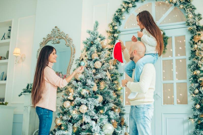 Ragazza sveglia e sua la madre che decorano abete sulla notte di Natale immagine stock